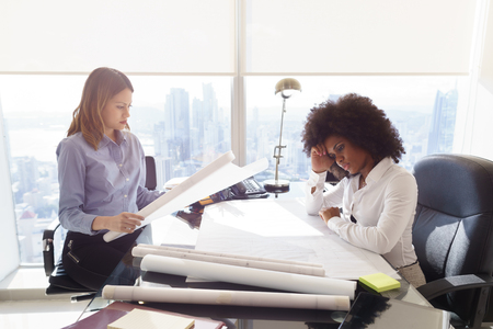 medium shot: Team of two female architects, sitting at desk in office skyscraper. The women talk reviewing a building plan. Medium shot