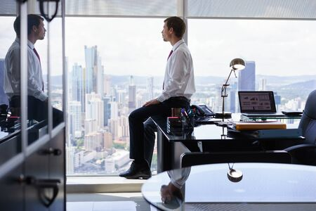 contemplates: Adult businessman sitting on desk in modern office and looking out of the window, with pensive expression. The man contemplates the city and skyscrapers. Stock Photo