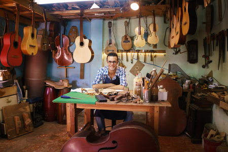 violin making: Lute maker shop and acoustic music instruments: portrait of a young adult artisan sitting at his desk and smiling at camera. He is surrounded by many guitars, mandolins and violins.