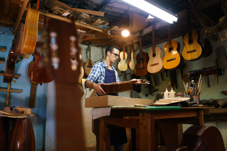 violin making: Lute maker shop and acoustic music instruments: a young adult artisan fixes an old classic guitar, then stores it in a cardboard case for his client. Wide shot Stock Photo