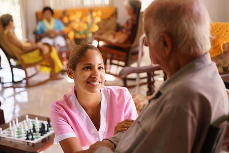 Los ancianos en cuidados paliativos: geriátrica joven atractiva mujer hispana que trabaja como enfermera cuida a un hombre mayor en silla de ruedas. Ella habla con él después desaparece para ayudar a otros pacientes