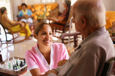 Old people in geriatric hospice: young attractive hispanic woman working as nurse takes care of a senior man on wheelchair. She talks with him then goes away to help other patients Stockfoto