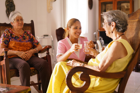 helps: Old people in geriatric hospice: young attractive hispanic woman working as nurse helps a senior woman. She gives a water glass and prescription medicine to the aged patient