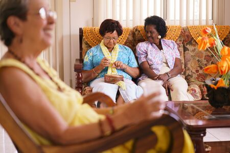 wrinkled: Old people in geriatric hospice: Senior woman sitting on sofa in hospital, knitting with ball of wool between other ladies. The aged grandma is pensive and focused on her hobby.
