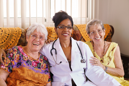 geriatric: Old people in geriatric hospice: Elderly man and woman hugging an african american doctor, showing a friendly relationship between personnel and patients.