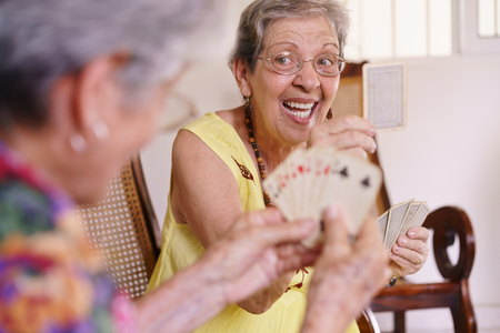 Old people in geriatric hospice: group of senior women playing cards and having fun together. An aged lady wins the game and shows a card to her rival Stockfoto