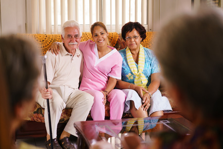 geriatric: Old people in geriatric hospice: Elderly man and woman hugging a young nurse, showing a friendly relationship between personnel and patients. Stock Photo