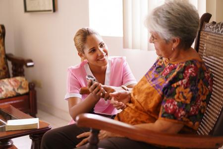 Oude mensen in geriatrische hospice: bejaarde dame met gezichtsproblemen het bekijken van het scherm van de mobiele telefoon. Een verpleegkundige helpt de senior vrouw een nummer op het kleine toetsenbord