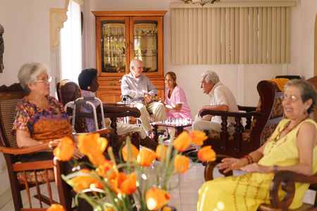 geriatric: Old people in geriatric hospice: young attractive hispanic woman working as nurse helps a senior man on wheelchair. He joins a group of friends playing chess and having fun