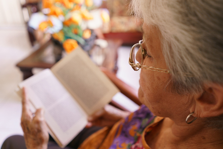 hospice: Old people in geriatric hospice: senior woman with eyeglasses and miopia problems sitting on chair and reading a book.