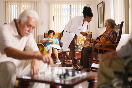 gerontology: Old people in geriatric hospice: Black doctor visiting an aged patient, measuring blood pressure of a senior woman. Group of retired men in foreground playing chess. Stock Photo