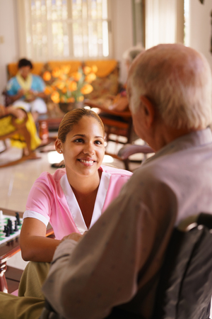geriatric: Old people in geriatric hospice: young attractive hispanic woman working as nurse takes care of a senior man on wheelchair. She talks with him then goes away to help other patients Stock Photo
