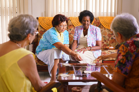 Oude mensen in geriatrische hospice: groep van hooggeplaatste vrouwen speelkaarten en plezier samen. De oude dames zitten op de bank van het ziekenhuis en start een nieuwe match