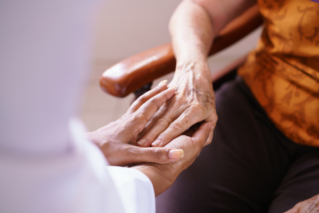 gerontology: Old people in geriatric hospice: Black doctor visiting an aged patient, holding hands of a senior woman. Concept of comfort and compassion