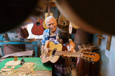 generation gap: Small family business and traditions: old grandpa with grandson in lute maker shop. The senior artisan gives teaches how to play classic guitar to the boy, who plays his first notes with the instrument Stock Photo