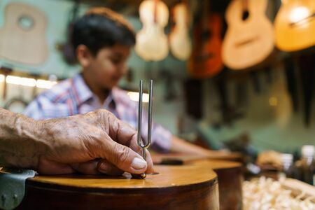 diapason: Small family business and traditions: old grandpa with grandson in lute maker shop. The senior artisan teaches how to tune a classic guitar to the boy. Closeup of hand holding a diapason on guitar body.