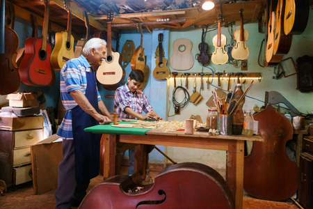 skill: Small family business and traditions: old grandpa with grandson in lute maker shop. The senior artisan teaches to the boy how to chisel wood to make a music instrument