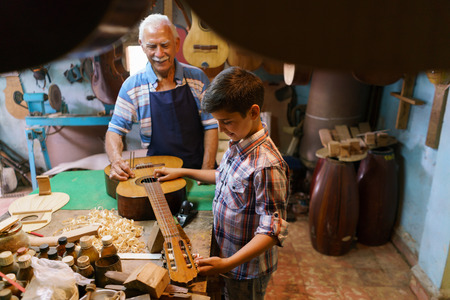 diapason: Small family business and traditions: old grandpa with grandson in lute maker shop. The senior artisan teaches how to tune a classic guitar to the boy, holding a diapason.