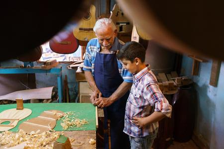 Klein familiebedrijf en tradities: oude opa met kleinzoon in luit maker winkel. De senior ambachtsman leert om de jongen hoe hout beitel om een muziekinstrument te maken