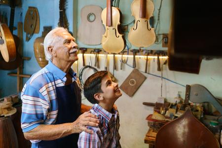 La pequeña empresa familiar y las tradiciones: abuelo con el nieto de edad en la tienda fabricante de laúd. El experto en la alta abraza al niño y le hace descubrir sus hechos a mano los instrumentos de guitarra y de la música.