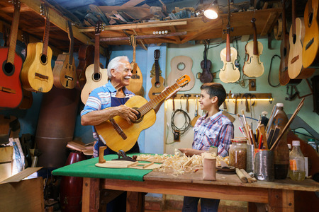 Small family business and traditions: old grandpa with grandson in lute maker shop. The senior artisan gives teaches how to play classic guitar to the boy, who looks carefully at the instrument