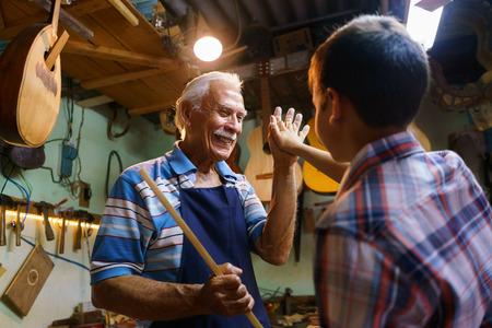 generation gap: Small family business and traditions: old grandpa with grandson in lute maker shop. The senior artisan gives five to the boy, who helps him to make a handmade music instrument Stock Photo