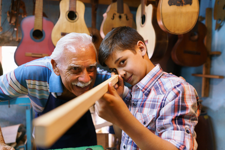 generation gap: Small family business and traditions: old grandpa with grandson in lute maker shop. The senior artisan teaches to the boy how to chisel wood to make a music instrument. The kid looks carefully at his work