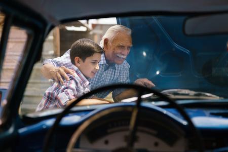 Familie en Generatiekloof. Oude opa tijd doorbrengen met zijn kleinzoon. De senior man toont de motor van een vintage auto van de jaren '60 tot de preteen kind. Ze lachen gelukkig. Gezien vanuit het interieur van de auto
