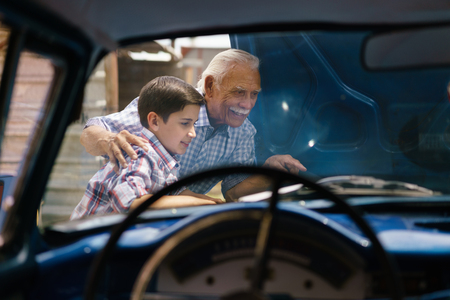 Family and Generation gap. Old grandpa spending time with his grandson. The senior man shows the engine of a vintage car from the 60s to the preteen child. They smile happy. Viewed from the interior of the car Standard-Bild