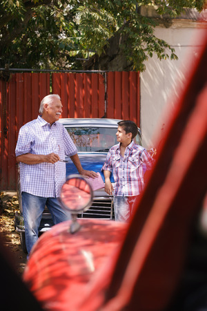 generation gap: Family and Generation gap. Old grandpa spending time with his grandson. The senior man talks vintage car with the boy and lean against the hood of an automobile from the 60s