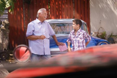Familie und Kluft zwischen den Generationen. Alte Großvater mit seinem Enkel verbringen Zeit. Der Senior Mann spricht Oldtimer mit dem Jungen und lehnen sich an die Motorhaube eines Autos aus den 60er Jahren Standard-Bild - 56097409