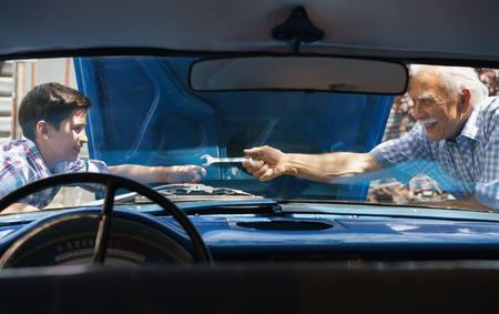 Famille et de l'écart de génération. Vieux-père de passer du temps avec son petit-fils. L'homme âgé demande à l'enfant préadolescent pour l'aider à fixer le moteur d'une voiture vintage des années 60. Ils sourient heureux. Vu de l'inter de la voiture Banque d'images - 56097410
