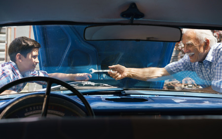 Family and Generation gap. Old grandpa spending time with his grandson. The senior man asks the preteen child to help him fixing the engine of a vintage car from the 60s. They smile happy. Viewed from the interior of the car