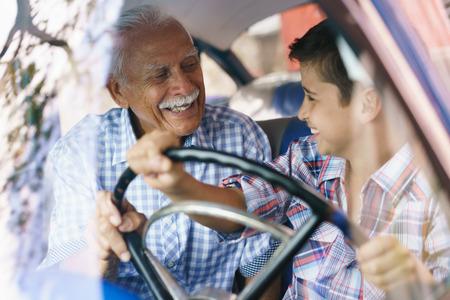 Famille et de l'écart de génération. Vieux-père passer du temps avec son petit-fils et de lui apprendre à conduire. Le garçon tient la Volante d'une voiture vintage des années 60. Ils ont tous deux sourire heureux regardant les uns les autres.