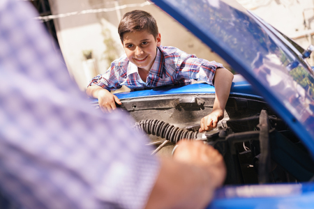 generation gap: Family and Generation gap. Old grandpa spending time with his grandson. The senior man teaches to the preteen child to fix the engine of a vintage car from the 60s. They smile happy.