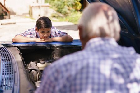 generation gap: Family and Generation gap. Old grandpa spending time with his grandson. The senior man shows the engine of a vintage car from the 60s to the preteen child. They boy smiles happy.