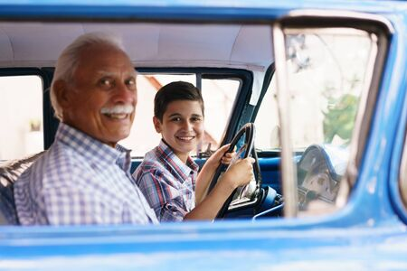 generation gap: Family and Generation gap. Old grandpa spending time with his grandson. He teaches him to drive. The boy holds the volante of a vintage car from the 60s. They both smile happy looking at camera. Stock Photo