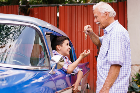 generation gap: Family and Generation gap. Old grandpa spending time with his grandson. The senior man gives the keys of a vintage car from the 60s to the preteen child sitting inside. They smile happy. Stock Photo