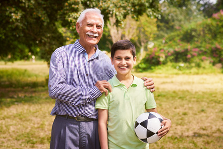 generation gap: Grandpa spending time with grandson: Portrait of senior man playing football with his grandchild in park. The old man embraces the young kid holding the ball, smiling and looking at camera Stock Photo