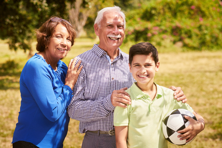generation gap: Grandparents spending time with grandson: Portrait of senior man and old woman playing football with grandchild in park. The old man embraces the young kid holding the ball, smiling and looking at camera Stock Photo