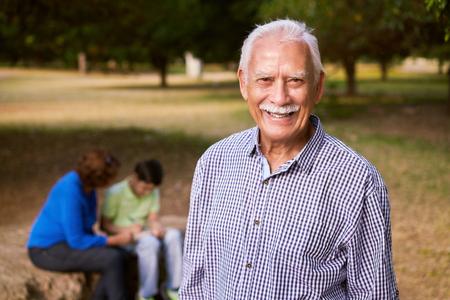 Großeltern erziehen Enkel: Ältere Frau und alter Mann verbringt viel Zeit mit ihrem Enkel im Park. Die alten Menschen helfen, den jugendlichen Jungen seiner Schule Hausaufgaben machen. Der Opa schaut lächelnd in die Kamera