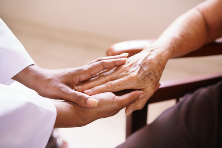 mujer trabajadora: Los ancianos en cuidados paliativos: geriátrica paciente envejecido recibe la visita de un médico negro femenina. Se estrechan las manos y hablan en el hospital.