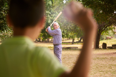 generation gap: Grandparents spending time with grandson: Senior man playing baseball with his grandson in park. The old man holds the bat, while the kid prepares to throw the ball Stock Photo