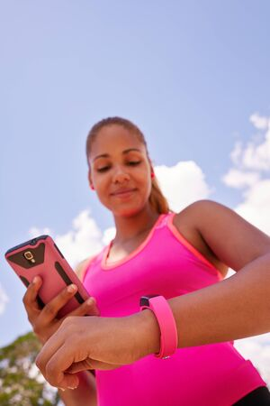 synchronizing: Young people doing sport activities, woman runner jogging programming fit watch and synchronizing data with mobile phone wirelessly