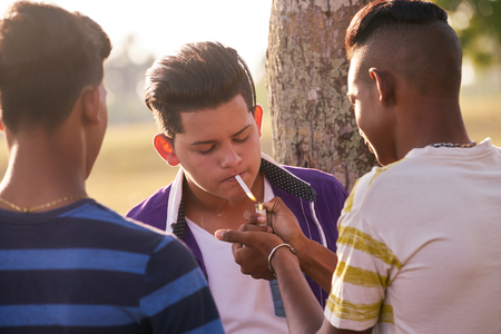 youth group: Youth culture, young people, group of male friends, mixed race teen outdoor, teenager in park. Hispanic kid smoking cigarette, confident boy, smoker. Health problems, social issues.