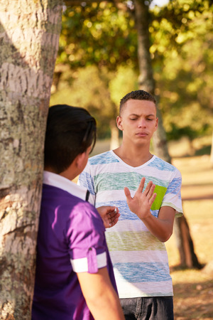 joven fumando: La cultura juvenil, los jóvenes, grupo de amigos varones, adolescentes multirraciales en el parque. Los niños que fuman el cigarrillo, los niños, los fumadores. Los problemas de salud, problemas sociales. Joven latino negarse a fumar.
