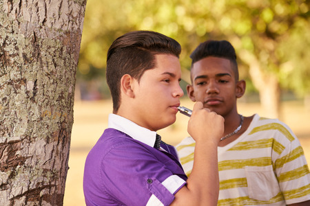 joven fumando: Youth culture, young people, group of male friends, multi-ethnic teens outdoors, multiracial boys together in park. Kids smoking electronic cigarette, e-cig smokers. Health problems, social issues