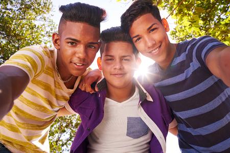 La cultura juvenil, los jóvenes, grupo de amigos varones adolescentes, multiétnicos al aire libre, adolescentes juntos en el parque. Retrato de los niños felices sonriendo, niños mirando a la cámara. Camara lenta Foto de archivo