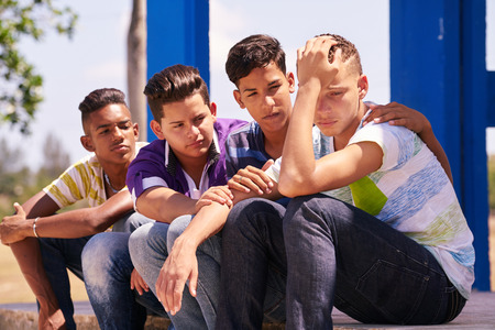 Youth culture, young people, group of male friends, multi-ethnic teens outdoor, teenagers together in park. Boys comforting sad friend, kids helping depressed boy. Adolescence bond, relationship Banque d'images