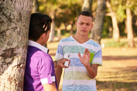 Youth culture, young people, male friends, multiethnic teens outdoors, multiracial teenagers together in park. Boys smoking electronic cigarette, e-cig smokers. Health problems, social issues Stockfoto